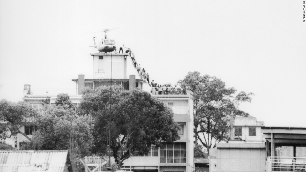 Hubert Van Es, a Dutch photojournalist working at the offices of United Press International, took this photo on April 29, 1975, of a CIA employee helping evacuees onto an Air America helicopter. It became one of the best known images of the U.S. evacuation of Saigon. Van Es never received royalties for the UPI-owned photo. The rights are owned by Bill Gates through his company, Corbis.