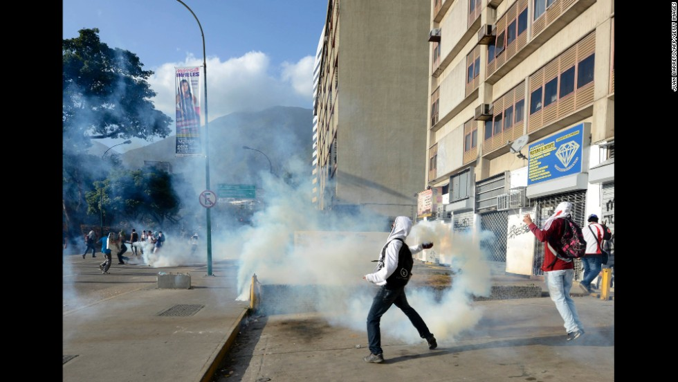 A protester throws a tear gas canister toward National Guard members in Caracas on March 4.