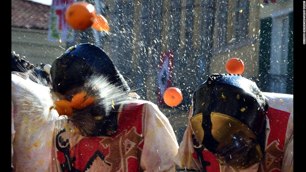 "Men with helmets are pelted by oranges Tuesday, March 4, during the traditional ""battle of the oranges"" that is held during the carnival in Ivrea, Italy."