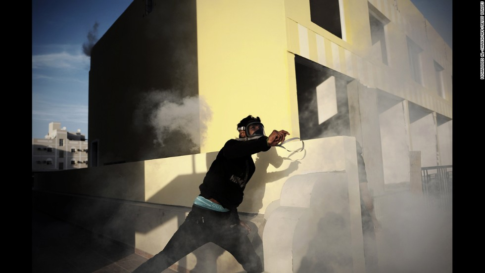 A protester throws a tear gas canister during clashes with riot police in the Bahraini village of Daih, west of the capital Manama, on Monday, March 3.