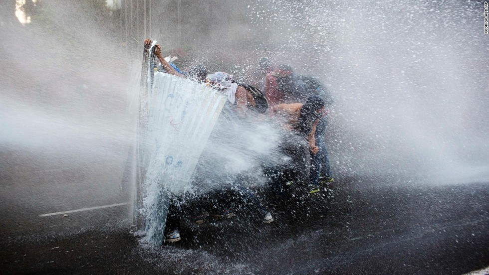 Anti-government demonstrators take cover from a police water cannon in Caracas, Venezuela, on Friday, February 28.