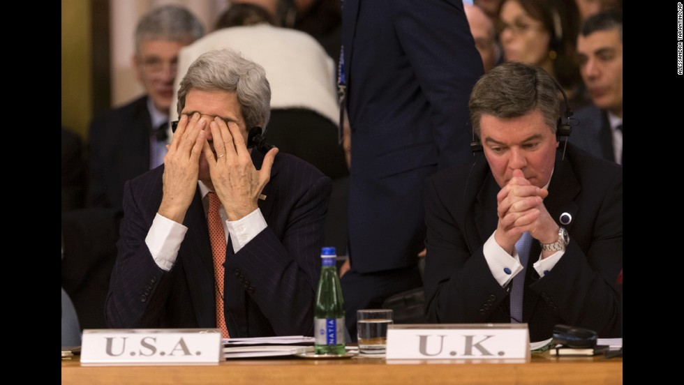 U.S. Secretary of State John Kerry, left, touches his face in Rome on Thursday, March 6, during the Conference on International Support to Libya. He is seated next to Hugh Robertson, the British minister of state for foreign and Commonwealth affairs.