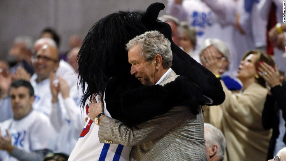 Former U.S. President George W. Bush gets a hug from Peruna, the mascot from Southern Methodist University, during a break in the men's basketball game between SMU and Louisville on Wednesday, March 5.