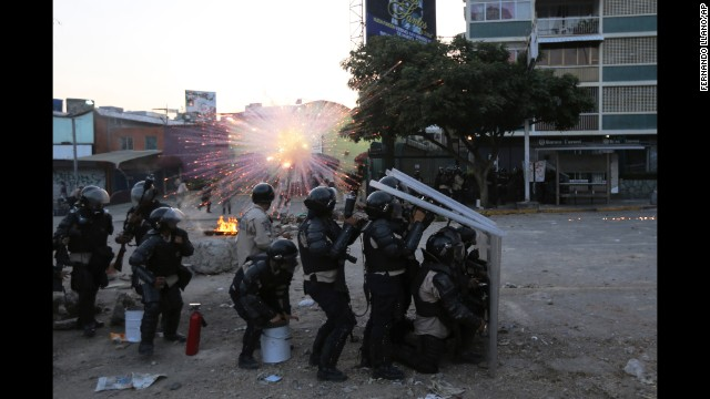 Bolivarian National Guard members take cover as a firecracker launched by protesters explodes nearby in Caracas on Wednesday, March 5.