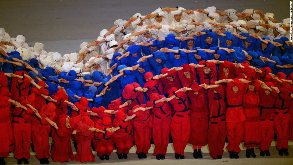 Performers simulate the Russian flag moving in the wind.