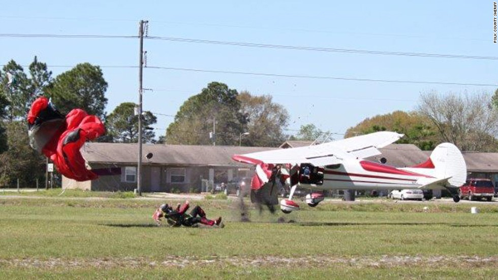 The Cessna lands upright beside the skydiver on the ground.
