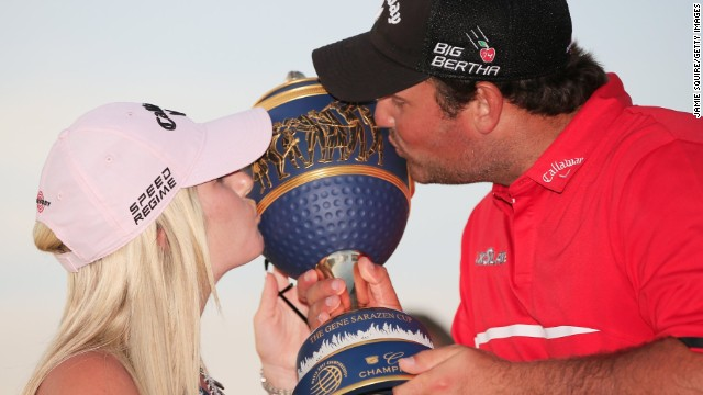 Patrick Reed celebrates his victory in Florida with his wife Justine as they kiss the Gene Sarazen trophy.
