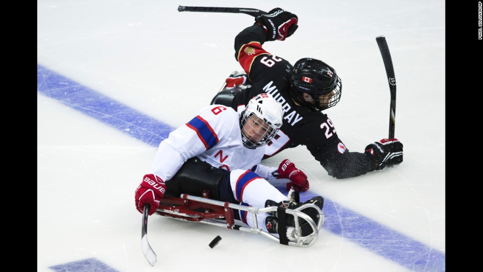 Graeme Murray of Canada and Emil Kirstistuen of Norway vie for the puck during an ice sledge hockey game on Sunday, March 9.