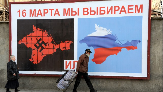 People walk past a poster in Sevastopol on March 11, 2014 reading 'On March 16 we will choose either... or...', depicting Crimea in red with a swastika and covered in barbed wire (L) and Crimea with the colors of the Russian flag.