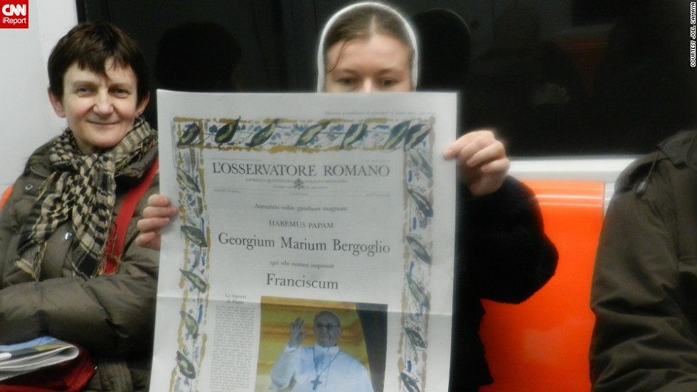 A nun reads a copy of the Vatican newspaper proclaiming Francis' election.