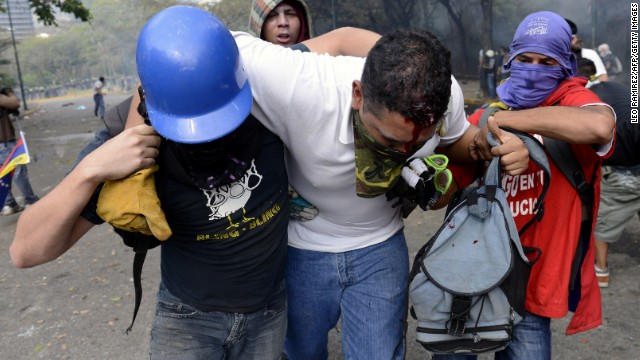 An injured protester is helped away in Caracas on March 12.