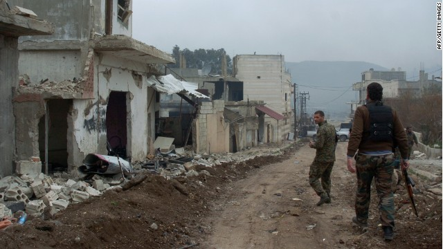Syrian forces patrol a street in the town of Zara, in the province of Homs, on March 8, 2014 during fighting against rebels.