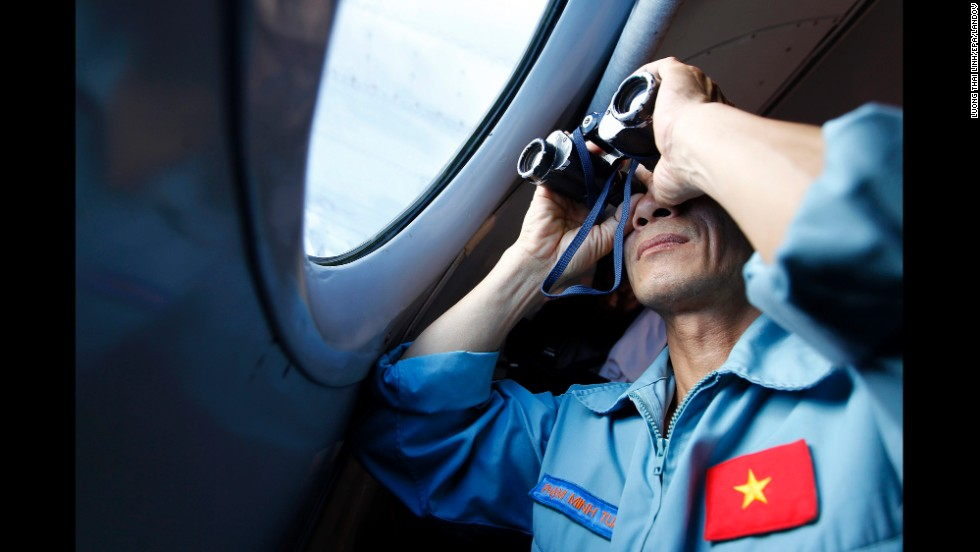 A Vietnamese military official looks out an aircraft window during search operations March 13, 2014.