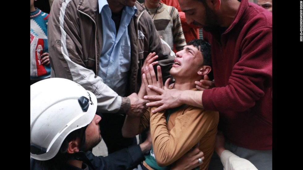 People attempt to comfort a man in Aleppo after a reported airstrike by government forces on Sunday, March 9.