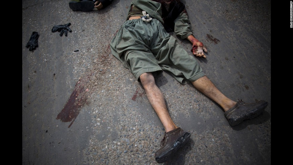 A dead suicide bomber lies on a street in Kandahar, Afghanistan, after an attack on the former Afghan intelligence headquarters on Wednesday, March 12.