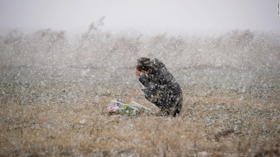 A woman in Rikuzentakata, Japan, prays in falling snow Tuesday, March 11, on the third anniversary of the devastating Tohoku earthquake and tsunami.