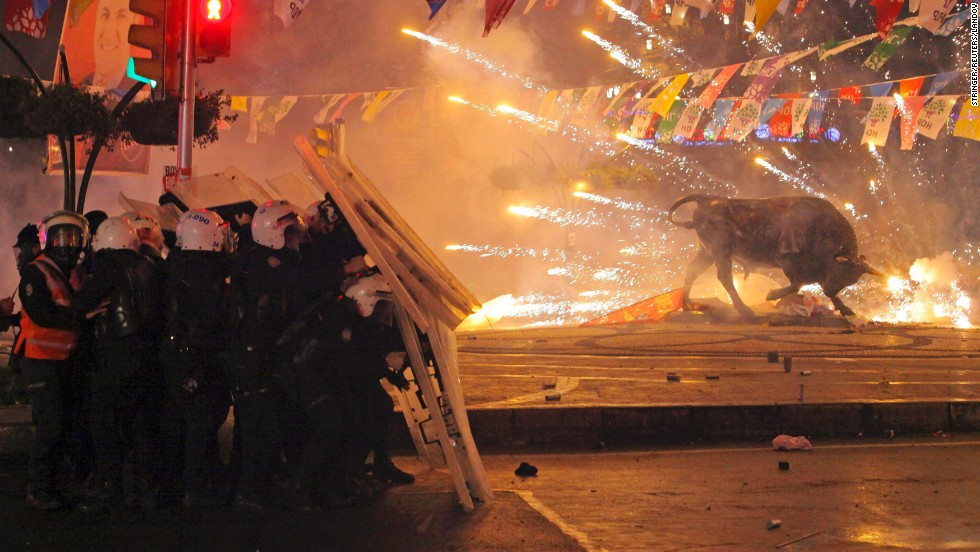 "Riot police in Istanbul shield themselves as fireworks thrown by anti-government protesters explode next to a statue of a bull on Tuesday, March 11. Protesters clashed with police across Turkey after <a href=""http://www.cnn.com/2014/03/13/world/europe/turkey-shooting-death/index.html"">the death of Berkin Elvan</a>, a 15-year-old boy who was critically wounded nine months ago after apparently being hit by a tear gas canister."