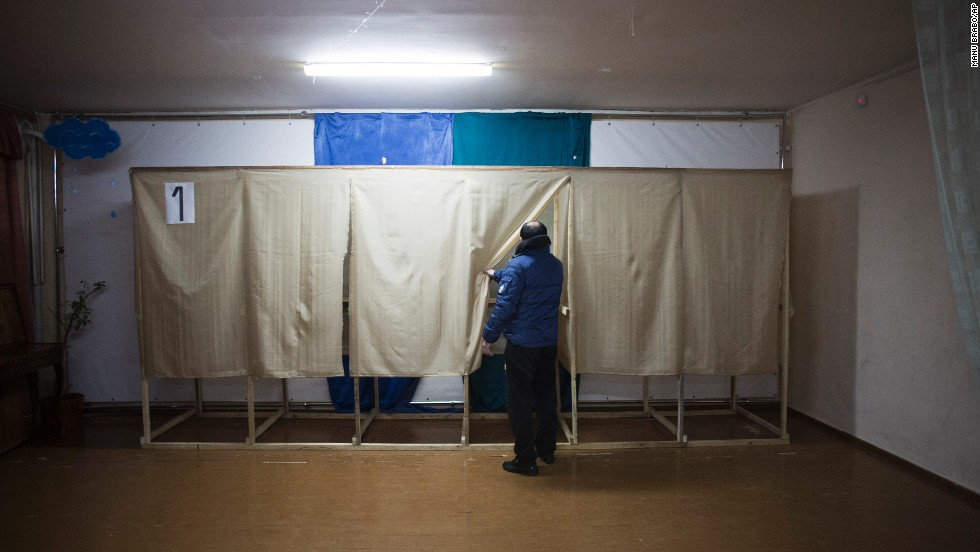 A member of a pro-Russian self-defense unit checks a polling station near Simferopol on March 13.