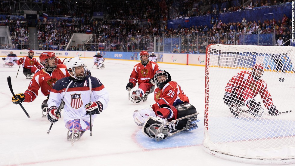Joshua Sweeney of the United States scores the game-winning goal past Vladimir Kamantcev of Russia during the ice sledge hockey gold medal game between the United States and Russia on March 15.