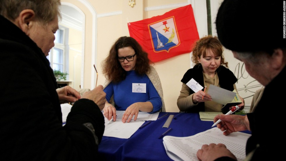 People sign up to receive their ballots from electoral staff at a polling station in Sevastopol.