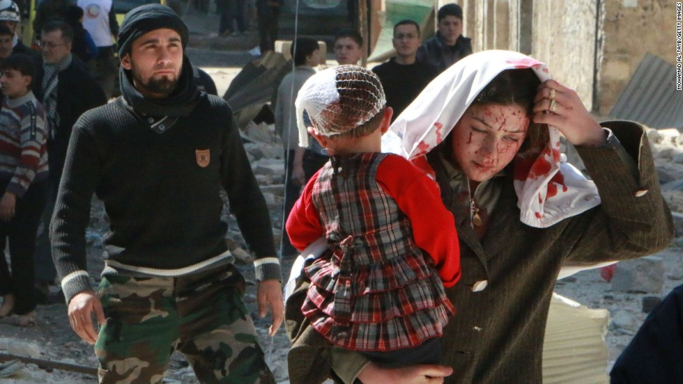 A woman with blood on her face carries a child following a reported airstrike by government forces Saturday, March 15, in Aleppo.