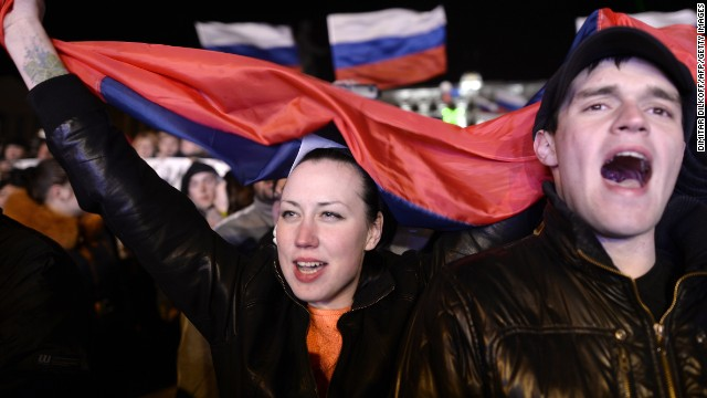 People sing the Russian national anthem as they celebrate in Simferopol's Lenin Square on March 16, 2014 after exit polls showed that about 95.5 percent of voters in Ukraine's Crimea region supported union with Russia. Crimeans voted overwhelmingly to join former political master Russia as tensions soared in the east of the splintered ex-Soviet nation amid the worst East-West crisis since the Cold War. AFP PHOTO / DIMITAR DILKOFF (Photo credit should read DIMITAR DILKOFF/AFP/Getty Images)