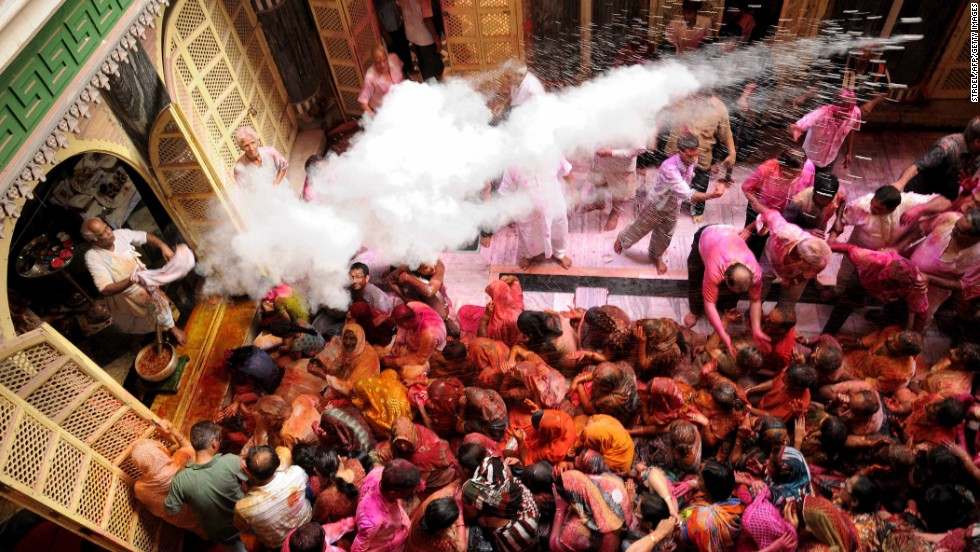 A priest throws colored powder over devotees as they celebrate Holi at the Radha Krishna temple in Kolkata on March 17.