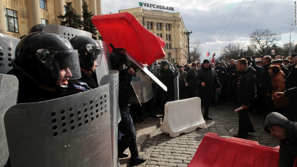 A Ukrainian police officer tries to shield himself from a road block thrown by pro-Russia supporters in Kharkiv on March 16.