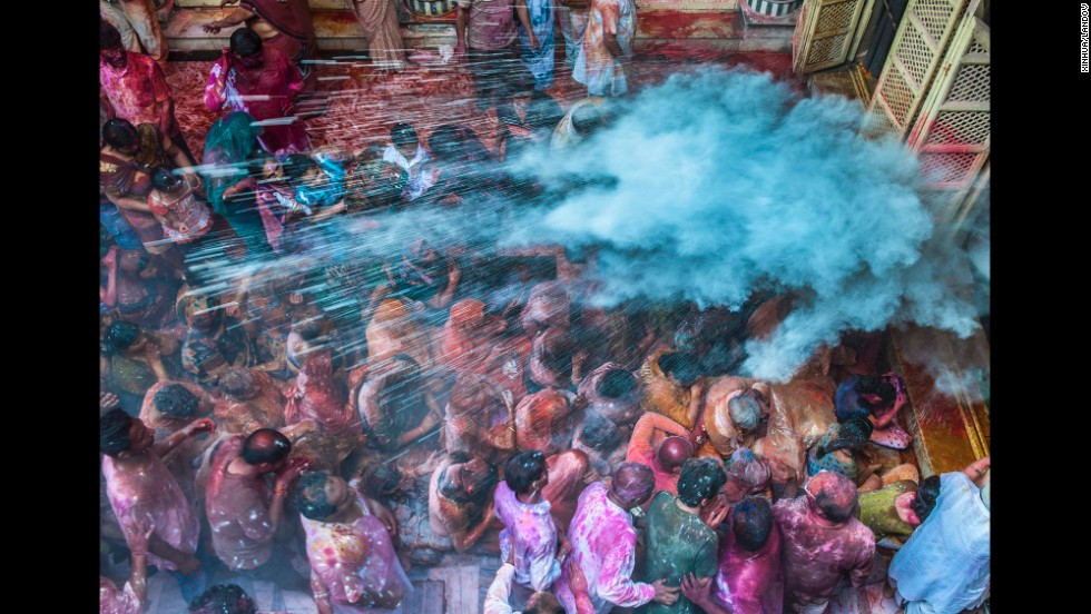 People throw colored powder on the crowds at a temple in Kolkata, India, on March 17.