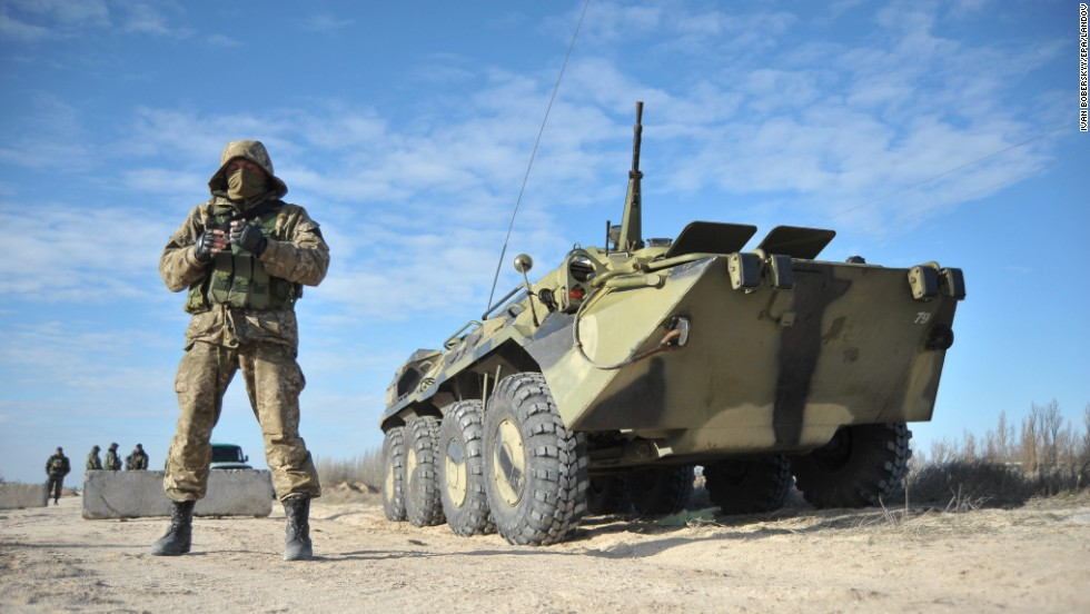 Ukrainian soldiers stand guard at a checkpoint near Strilkove, Ukraine, close to Crimea on Monday, March 17.