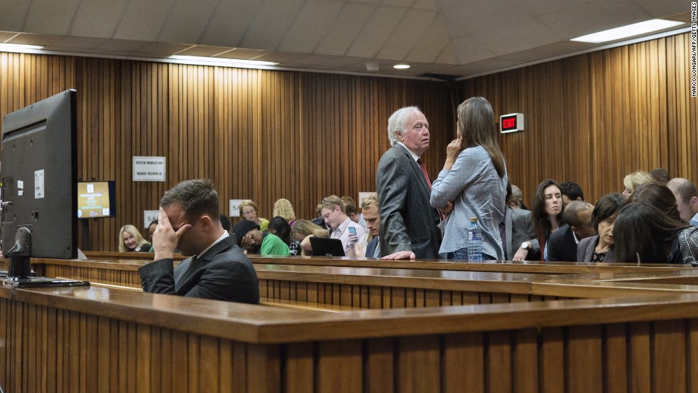 Pistorius holds his head while members of his family talk behind him on Tuesday, March 18.
