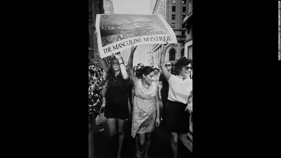 Steinem, left, helps hold up an image of the My Lai Massacre during a 1970 march down New York's Fifth Avenue.
