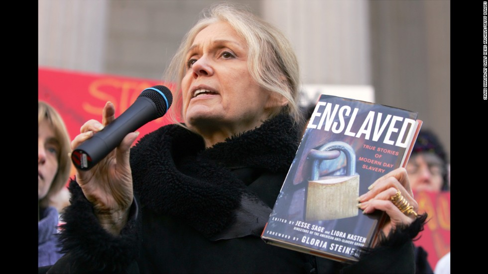 "Steinem holds up a copy of her book ""Enslaved"" as she speaks during a 2007 protest on the steps of the state Supreme Court in Albany, New York."