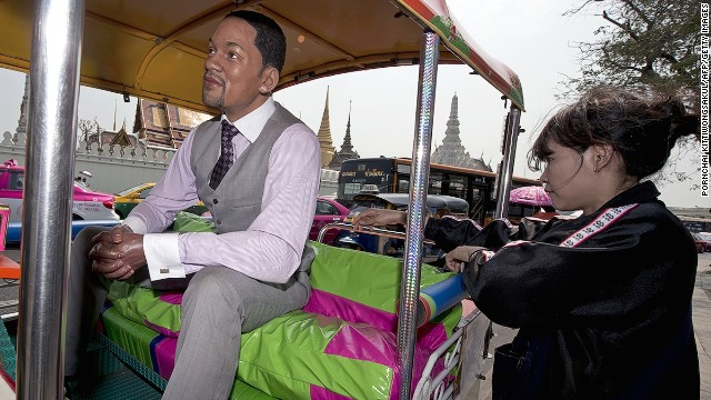 A woman checks out a wax sculpture of U.S. actor Will Smith sitting in a tuk-tuk outside Bangkok's Temple of the Emerald Buddha. Madame Tussauds Bangkok set up the sculptures to promote the museum to tourists in the wake of the political crisis.
