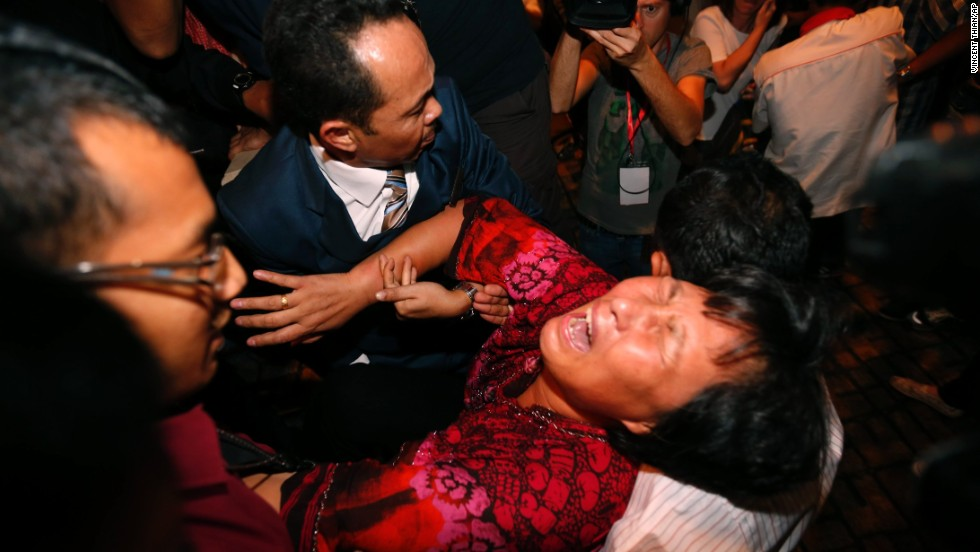 "A distraught relative of a passenger on the missing <a href=""http://www.cnn.com/2014/03/07/asia/gallery/malaysia-airliner/index.html"">Malaysia Airlines Flight 370</a> is carried out by security officials before a press conference in Sepang, Malaysia, on Wednesday, March 19. The plane disappeared during a March 8 flight from Kuala Lumpur to Beijing."