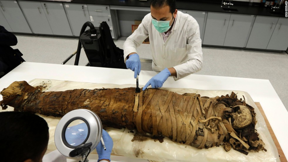 Conservators clean a female mummy dated to Pharaonic late period, between 712-323 BC, in the conservation center of Egypt's Grand Museum just outside of Cairo on Monday, March 17.