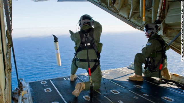 Royal Australian Air Force Loadmasters, Sergeant Adam Roberts (left) and Flight Sergeant John Mancey, launch a Self Locating Data Marker Buoy from a C-130J Hercules aircraft in the southern Indian Ocean as part of the Australian Defence Force's assistance to the search for Malaysia Airlines flight MH370.