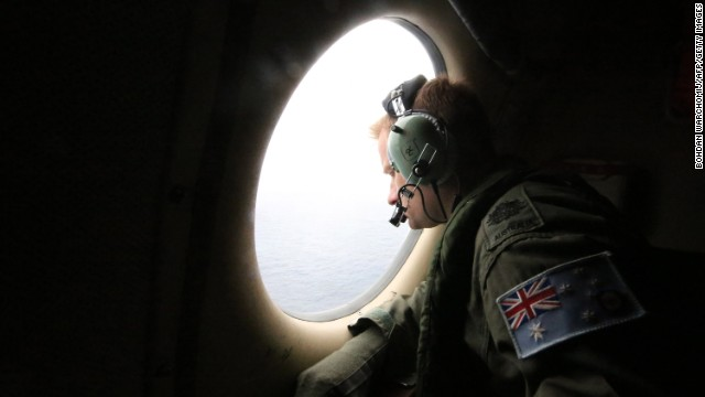 A crew member on a Royal Australian Air Force AP-3C Orion aircraft looks out a window during the Australian Maritime Safety Authority-led search for Malaysia Airlines Flight MH370 in the Southern Indian Ocean on Friday, March 21.