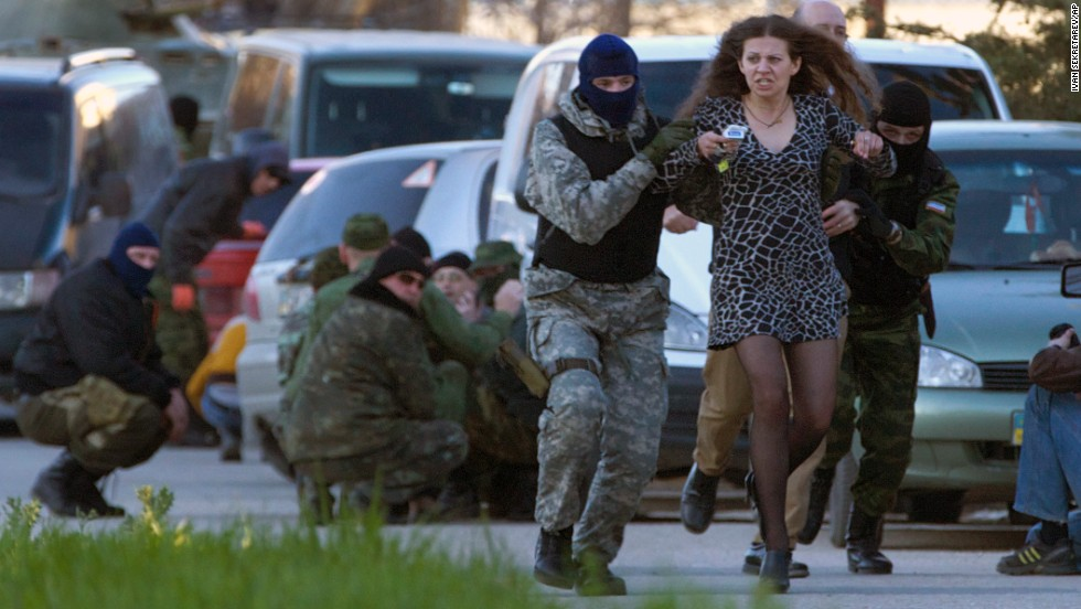 Pro-Russian militia members remove a resident as Russian troops assault the Belbek air base, outside Sevastopol, on Saturday, March 22. After its annexation of Crimea, Russian forces have consolidated their control of the region.