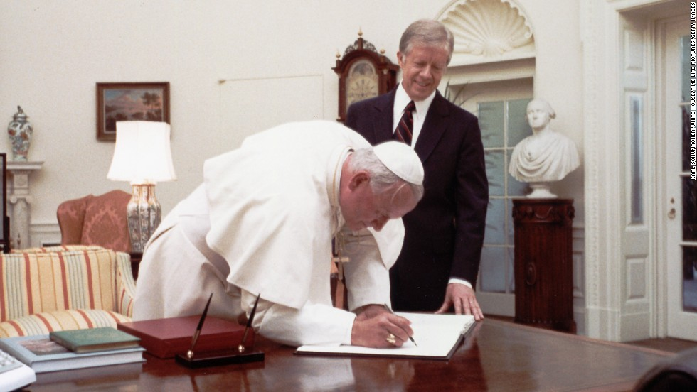 President Jimmy Carter watches Pope John Paul II sign the White House guest book in 1979. He was the first Pope to visit the White House.