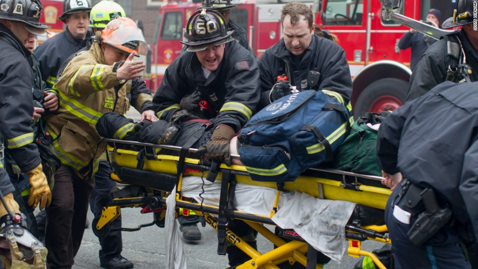 Firefighters and emergency medical personnel rush a firefighter from the scene March 26.