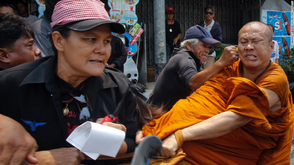 "Members of the pro-government ""red shirt"" movement attack a Buddhist monk on the outskirts of Bangkok, Thailand, on Monday, March 24. The monk was attacked after he shouted complaints to group members blocking a road near the office of the National Anti-Corruption Commission."