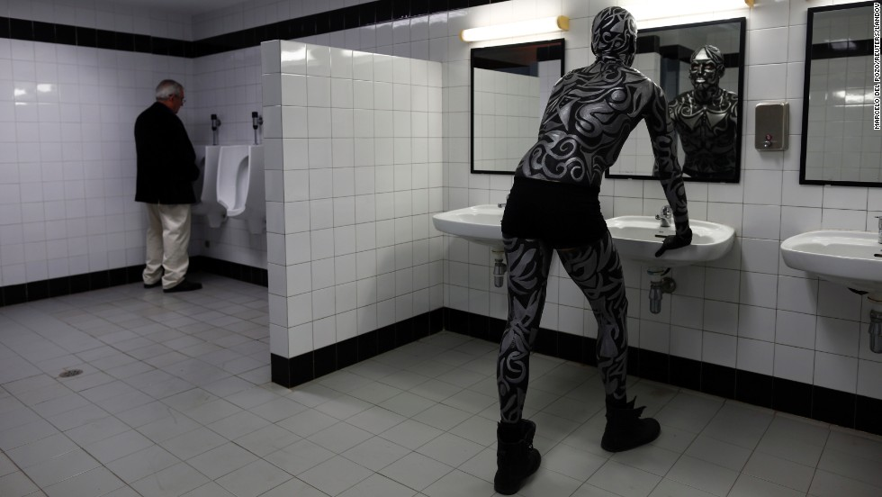 Ruben Hidalgo looks at his reflection before taking part in a body paint pageant in Seville, Spain, on Monday, March 24.