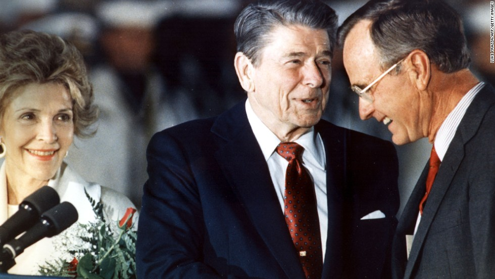 Reagan shakes hands with Bush in 1988 as first lady Nancy Reagan looks on. Bush served as Reagan's vice president from 1981 to 1989.