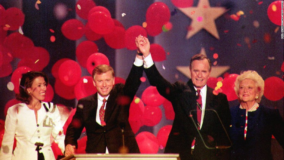 Bush and Quayle join hands at the August 1992 Republican National Convention in Houston. They are joined by their wives, Marilyn Quayle and first lady Barbara Bush.