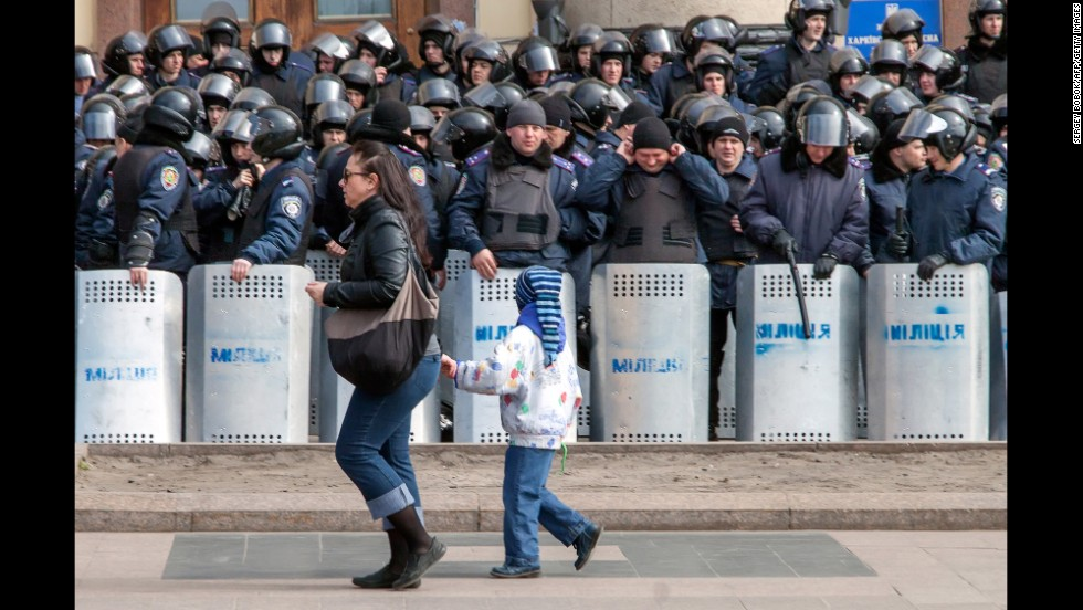 A woman and child walk past a line of police officers during a rally in Kharkiv on March 30.