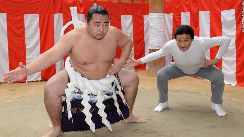 Sumo wrestler Kakuryu, left, and stable master Takanohana practice a ring purification ritual Thursday, March 27, in Osaka, Japan.