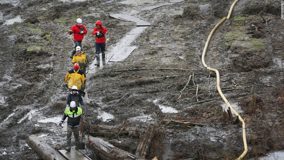 Search-and-rescue teams use a path of plywood to walk through a muddy field in Arlington, Washington, on March 30.