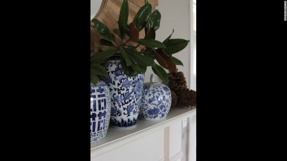 Blue chinoiserie ginger jars are a recent evolution of Clark's love of blue decor. Magnolia branches and pine cones in addition to the jars bring organic texture to her mantle.