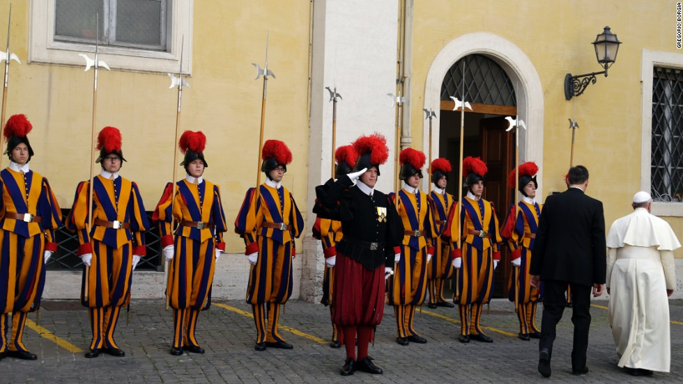 Pope Francis walks past Swiss Guards after the meeting.